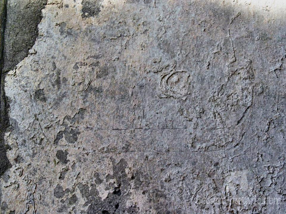 Medieval etching of ship on the wall plaster in the choir. A long low hull with high prow and stern and one mast amidship